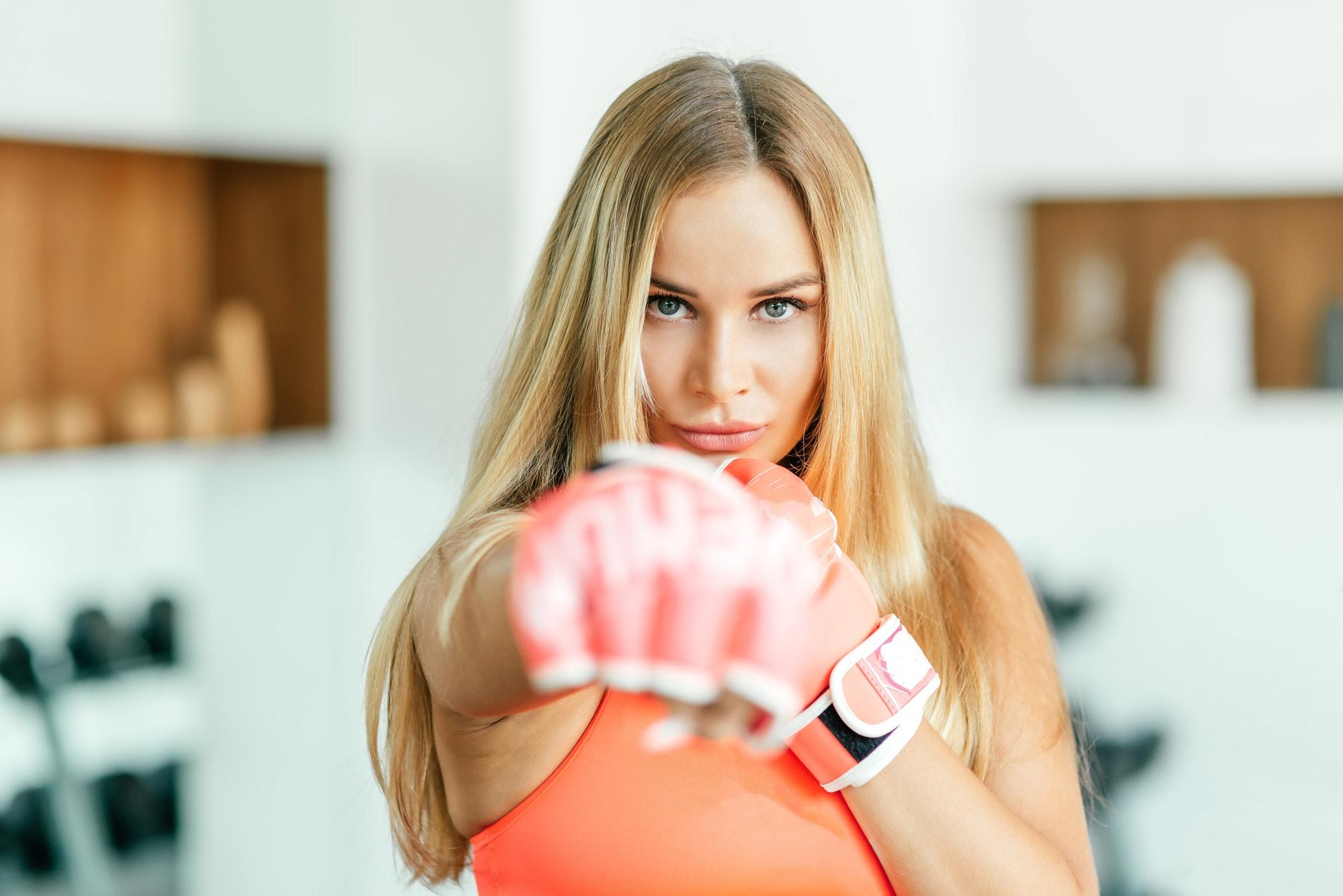 Dangerous girl. Sportswoman working out in gym.